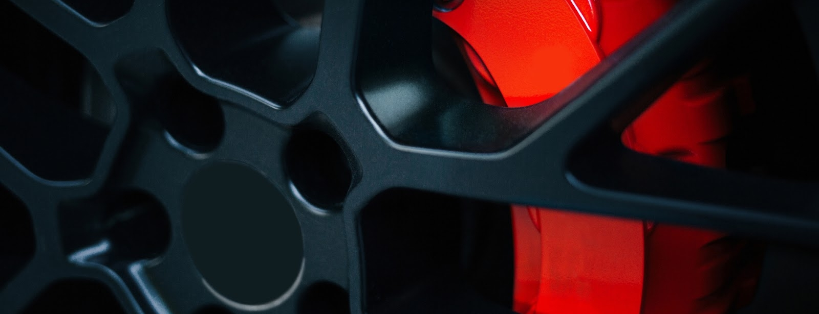 Close up of black wheel rim with red disk brakes